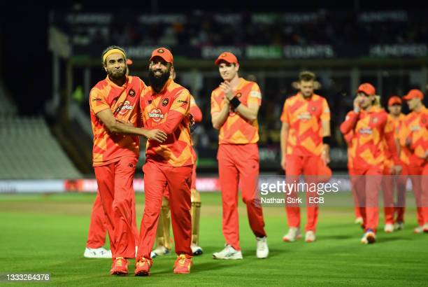 Imran Tahir of Birmingham Phoenix Men interacts with team mate Moeen Ali as they make their way off after taking five wickets including a hat trick...