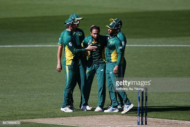Imran Tahir of South Africa celebrates with teammates for the wicket of Tim Southee of New Zealand during game five of the One Day International...
