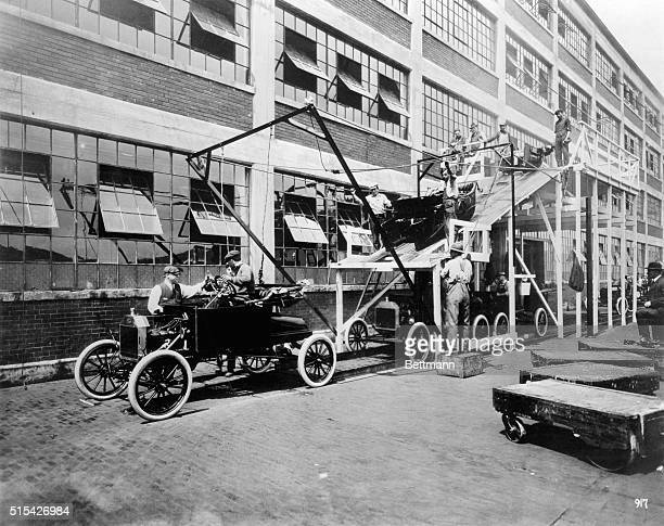In 1913 this was final assembly line at the Ford Motor Company's Highland Park plant Bodies were skidded down the wooden ramp and lowered onto the...