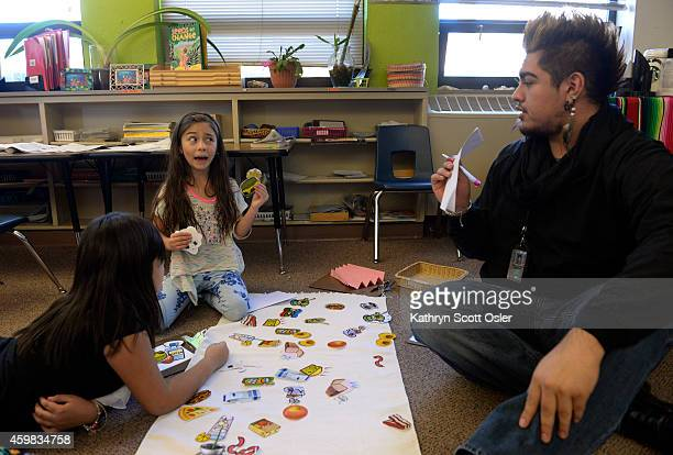 In a 13 grade classroom assistant teacher Alberto Sandoval right works with Maria Coronado Castorena left and Lyric Mora in picking healthy food...