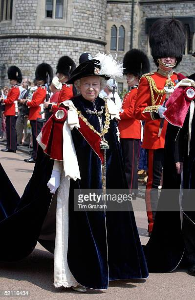 In A Black Velvet Hat With Ostrich Feather Queen Elizabeth II Clothed In The Heavy Traditional Robes Of The Most Noble Order Of The Garter Walked In...