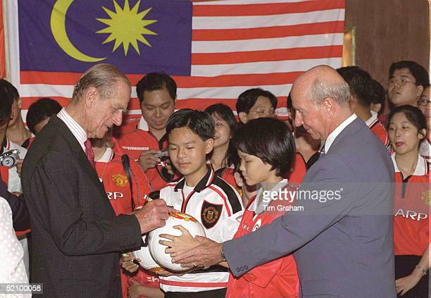 In A Break With Royal Tradition Prince Philip Puts His Signature On A Football For A Manchester United Football Fan Inside The Petronas Twin Towers...