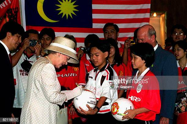 In A Break With Royal Tradition The Queen Agrees To Sign A Football For A Manchester United Football Fan Inside The Petronas Twin Towers Building...