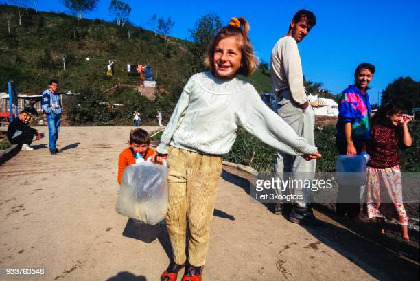 In a camp for refugees from the Bosnian War a girl carries water supplied by a UN relief agency Croatia 1997
