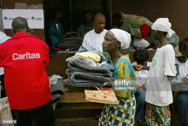 In a camp for those displaced by war, people receive relief items by the aid group Caritas August 30, 2003 in Monrovia, Liberia. After a month of...
