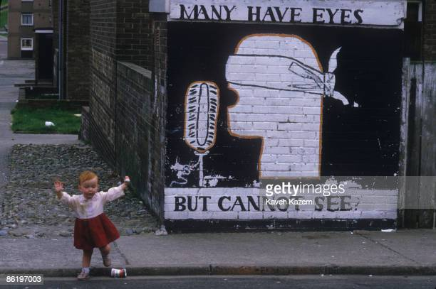 In a Catholic residential area of Derry , Northern Ireland, a little girl crosses the street in front of a mural criticizing the media, 23rd...