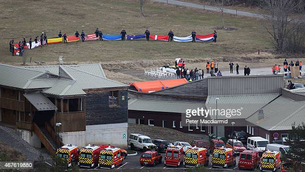 In a ceremony believed to be for relatives of the deceased of the crashed Germanwings flight emergency workers hold flags of the nations of those who...