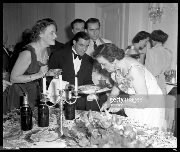 In a charming hostess gown of white lace Mrs Perle Mesta serves her guests at the first big party in the little house in Luxembourg where she...