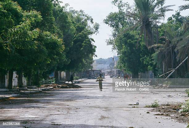 In a city torn by clan violence drought and hunger a lone Somali walks down a deserted street in Mogadishu before the arrival of 28000 United States...