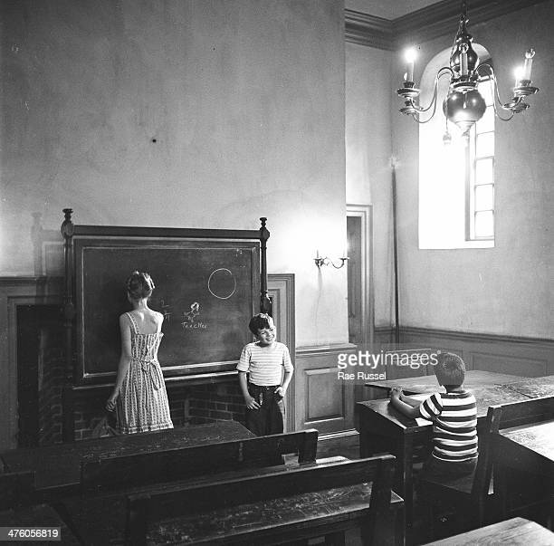 In a classroom in the Wren Building at the College of William and Mary an older girl writes on a chalkboard as two boys plays student and teacher...