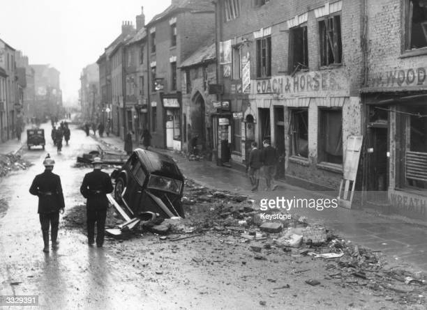 In a Coventry street lined with bomb damaged buildings a car has nosedived into a road after an airraid