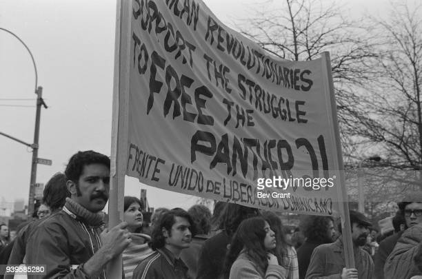 In a crowd a pair of men hold a banner that reads in part 'Dominican Revolutionaries Support the Struggle to Free the Panther 21' during a...