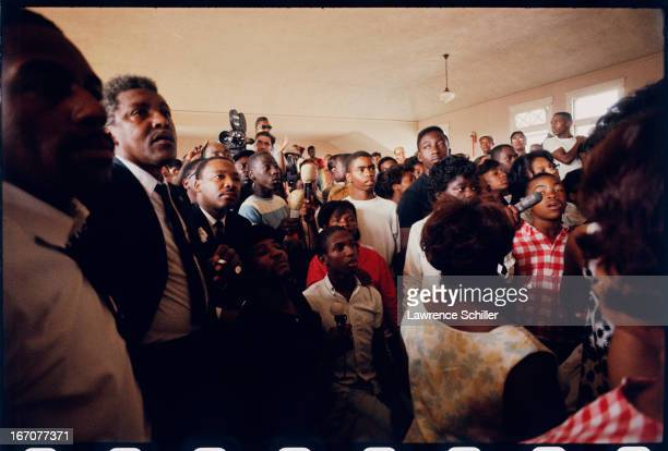 In a crowded room American Civil Rights and religious leader Dr Martin Luther King Jr listen to an unseen speaker during the Watts riots Los Angeles...