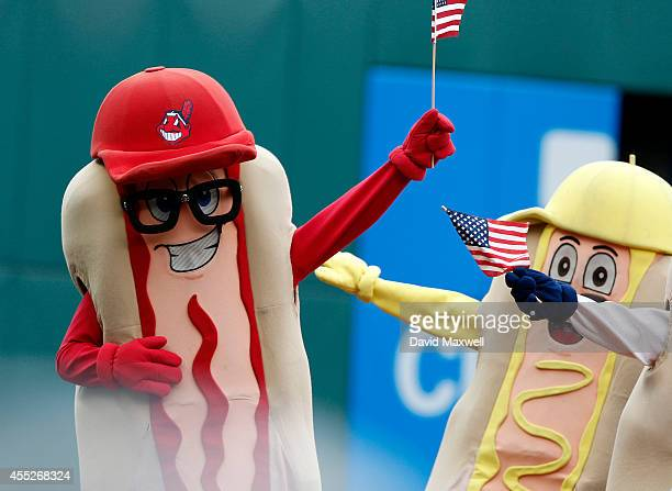 In a display of patriotism mascots cary American flags during the hot dog race during the seventh inning stretch of the game between the Cleveland...