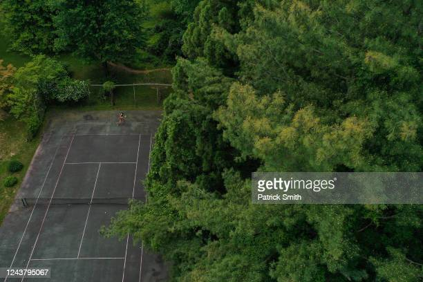 In a drone aerial view WTA Tennis player Sophie Chang of the United States returns balls that are served by her father via a tennis ball machine at...