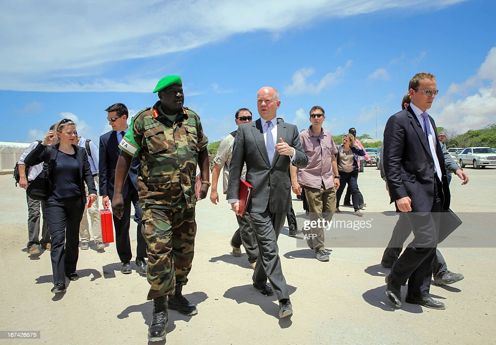 In a handout photograph taken and released by the African Union-United Nations Information Support Team on April 25, 2013,British Foreign Secretary William Hague (C) walks with African Union Mission in Somalia (AMISOM) Force Commander Lt. Gen Andrew Gutti (left) inside the AU mission's headquarters in the Somali capital Mogadishu. Britain's Foreign Secretary William Hague on Thursday opened a new embassy in Mogadishu after a 22-year absence, becoming the first EU nation to return to conflict-torn Somalia. Hague raised the Union Jack flag over the new mission at Mogadishu's airport in a surprise visit with Somali President Hassan Sheikh Mohamud. CREDIT 'AFP PHOTO / AU-UN IST PHOTO / STUART PRICE' - NO