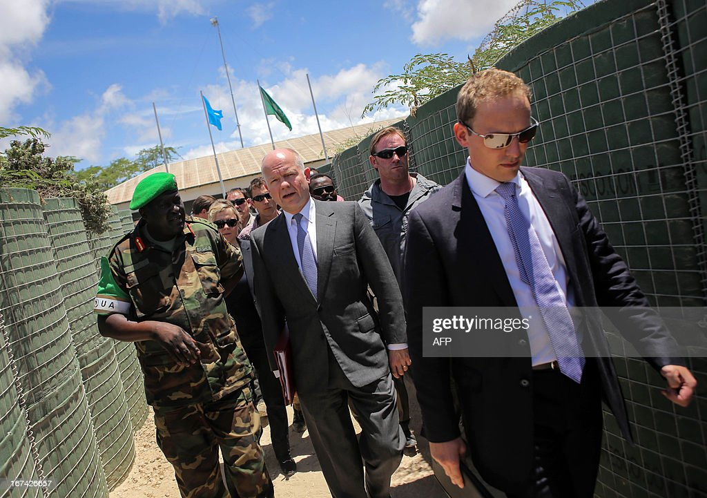 In a handout photograph taken and released by the African Union-United Nations Information Support Team on April 25, 2013,British Foreign Secretary William Hague (centre) walks with African Union Mission in Somalia (AMISOM) Force Commander Lt. Gen Andrew Gutti (left) inside the AU mission's headquarters in the Somali capital Mogadishu. Britain's Foreign Secretary William Hague on Thursday opened a new embassy in Mogadishu after a 22-year absence, becoming the first EU nation to return to conflict-torn Somalia. Hague raised the Union Jack flag over the new mission at Mogadishu's airport in a surprise visit with Somali President Hassan Sheikh Mohamud. CREDIT 'AFP PHOTO / AU-UN IST PHOTO / STUART PRICE' - NO