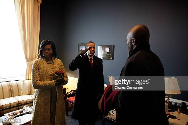 In a holding room at the Capital Barack H Obama practices his salute with aide Reggie Love and wife Michelle before he is sworn in by Chief Justice...