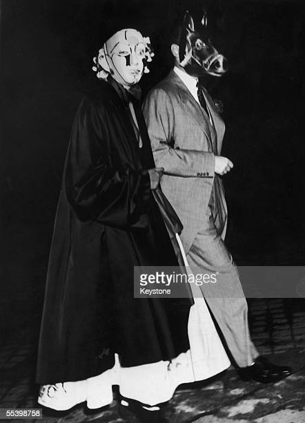 In a horse-head mask, British politician, diplomat and author Alfred Duff Cooper, 1st Viscount Norwich escorts a woman to a masked ball given in...