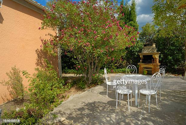 In a landscaped garden terrace with barbecue, tabl