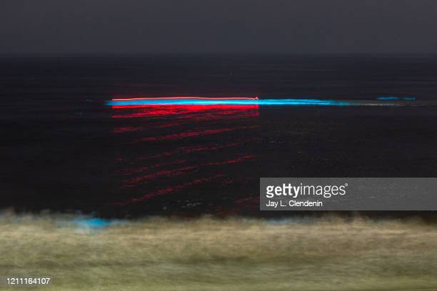 In a long exposure a boat is seen moving across the water and activating the blue bioluminescence in wave off the coast of Redondo Beach CA Monday...