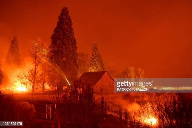 In a long exposure image, firefighters use a hose line to extinguish hot spots surrounding a structure off Highway 395 as the night sky during the...