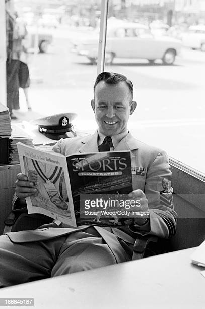 In a Manhattan shop window a soldier smiles as he looks through the premiere issue of Sports Illustrated magazine New York New York August 16 1954