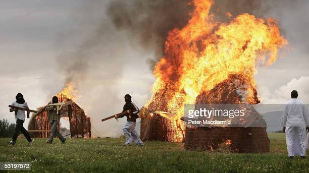 In a message to G8 leaders Darfur survivors burn villlage huts in a recreation of atrocities commited in Sudan on July 5 2005 in Auchterarder...