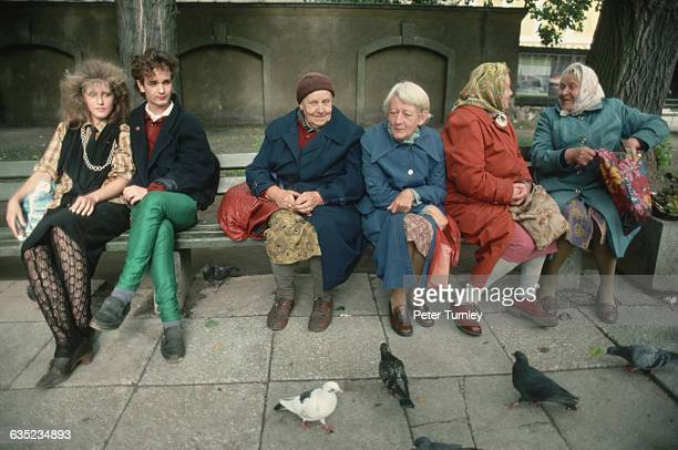 In a moment illustrating the generation gap a young couple sits slightly apart from a group of elderly women on a park bench in Moscow