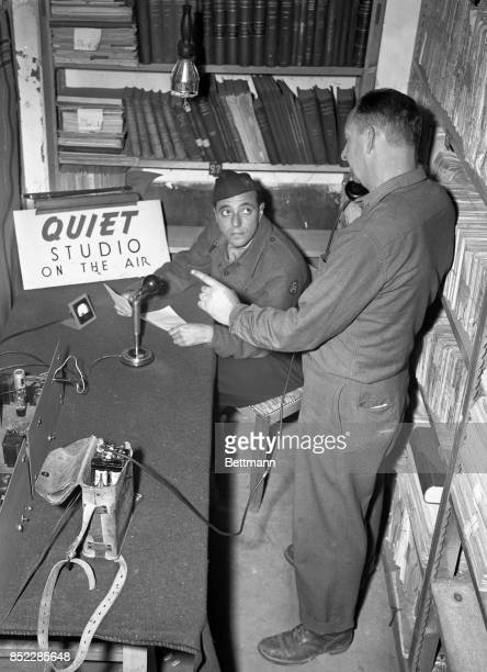 In a Nazi military library near Paris that is being used as a studio Larry Lesueur waits for the cue from Bill Hanford a Press Wireless employee...