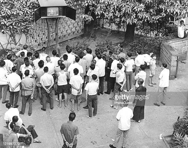 In a park viewers gather around to watch the television broadcast of the Apollo 11 moon landing Hong Kong July 1969