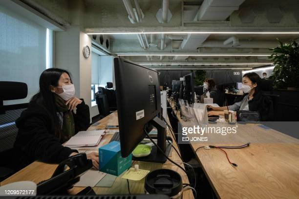 In a photo taken on April 9 2020 employees at their desks beside empty spaces as part of proctective measures against the spead of the COVID19 novel...