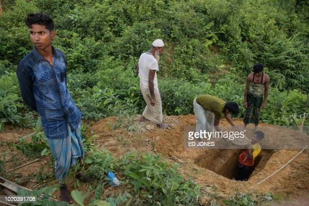 In a photo taken on August 10 Rohingya refugees prepare a grave for their neighbour who died that day at the Kutupalong refugee camp near Cox's Bazar...