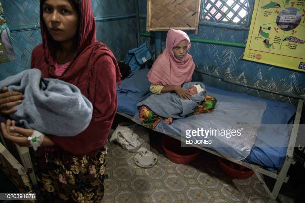 In a photo taken on August 14 2018 Rohingya refugees Zarina Begum and Latifa Begum hold their hoursold babies as they recover at an NGOrun maternity...