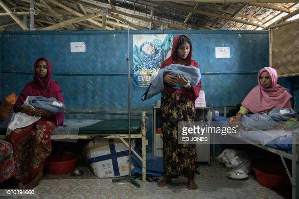 In a photo taken on August 14 Rohingya refugees Fatena Khatun Zarina Begum and Latifa Begum hold their hoursold babies as they recover at an NGOrun...