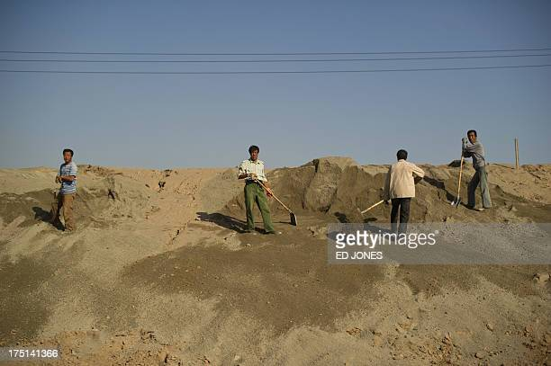 In a photo taken on August 19 2012 workers stand on a roadside near a 'toxic lake' surrounded by rare earth refineries near the inner Mongolian city...