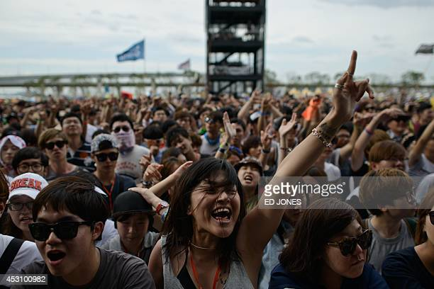In a photo taken on August 2 a fan gestures during a performance by South Korean metal band Crash at the Pentaport Rock Festival in Incheon The...