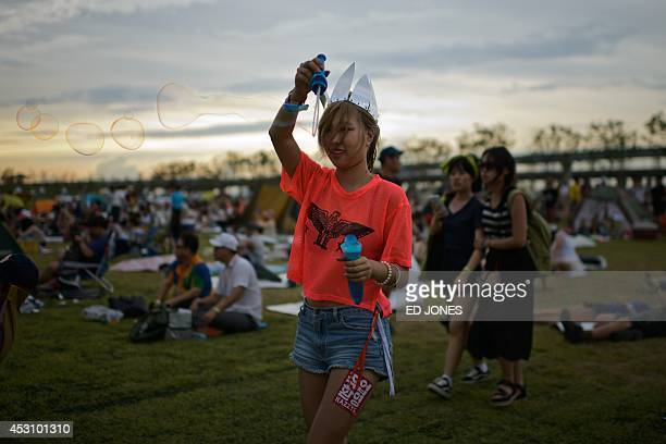 In a photo taken on August 2 a reveller creates bubbles at the Pentaport Rock Festival in Incheon The annual threeday Pentaport festival is...