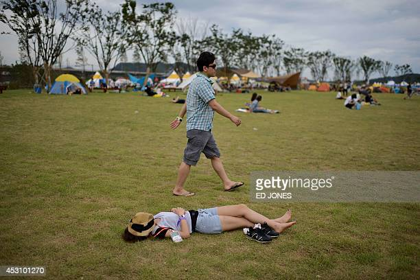 In a photo taken on August 2 a reveller sleeps at the Pentaport Rock Festival in Incheon The annual threeday Pentaport festival is considered South...