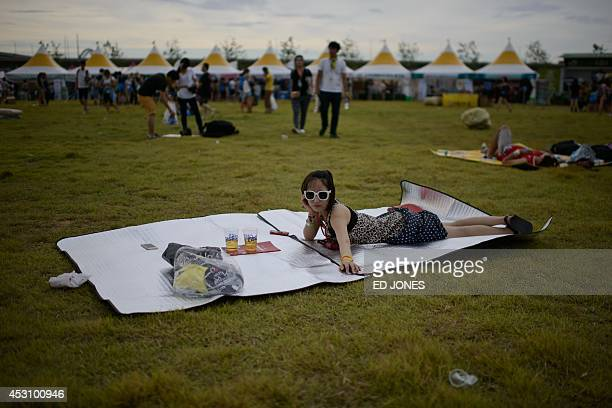 In a photo taken on August 2 a reveller waits for a band at the Pentaport Rock Festival in Incheon The annual threeday Pentaport festival is...