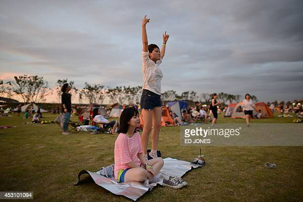 In a photo taken on August 2 revellers listen to a band perform at the Pentaport Rock Festival in Incheon The annual threeday Pentaport festival is...