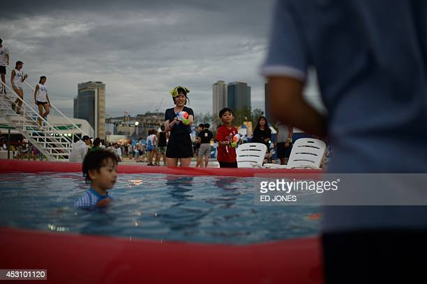 In a photo taken on August 2 revellers play with water guns at the Pentaport Rock Festival in Incheon The annual threeday Pentaport festival is...