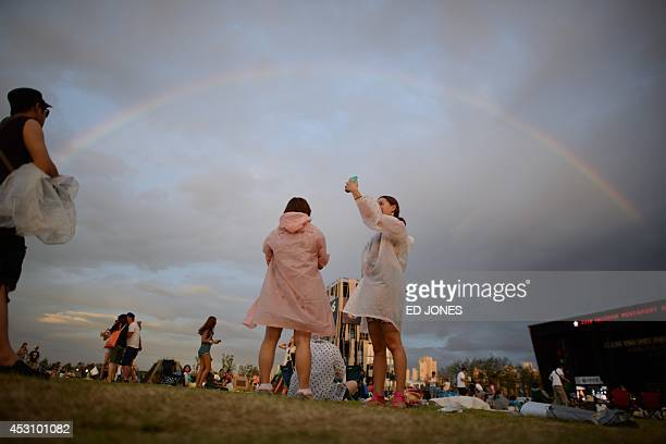 In a photo taken on August 2 revellers take photos beneath a rainbow at the Pentaport Rock Festival in Incheon The annual threeday Pentaport festival...