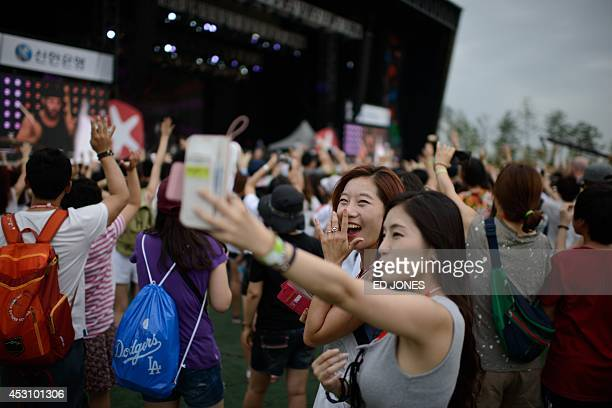 In a photo taken on August 2 revellers take 'selfies' during a performance by US band 'Boys Like Girls' on the main stage at the Pentaport Rock...