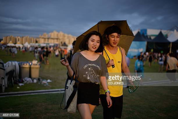 In a photo taken on August 2 revellers walk between stages at the Pentaport Rock Festival in Incheon The annual threeday Pentaport festival is...