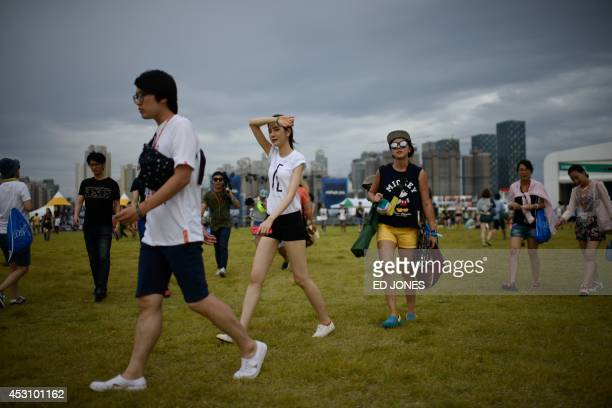 In a photo taken on August 2 revellers walk between venues at the Pentaport Rock Festival in Incheon The annual threeday Pentaport festival is...