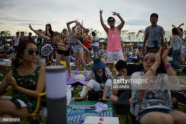 In a photo taken on August 2 revellers watch a performance by US band 'Boys Like Girls' on the main stage at the Pentaport Rock Festival in Incheon...
