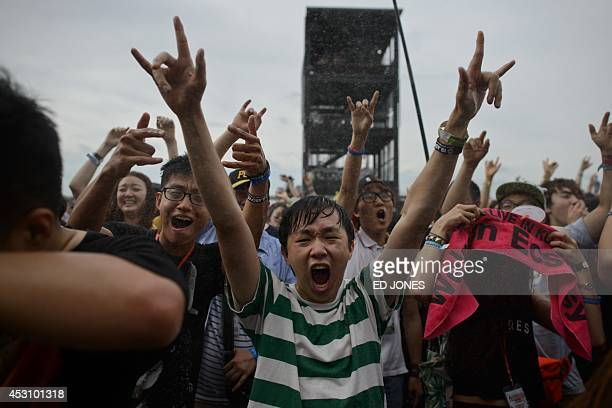 In a photo taken on August 2 rock fans gesture as they are sprayed with water during a performance by South Korean metal band Crash at the Pentaport...