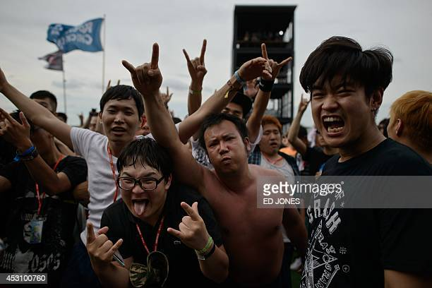 In a photo taken on August 2 rock fans gesture during a performance by South Korean metal band Crash at the Pentaport Rock Festival in Incheon The...