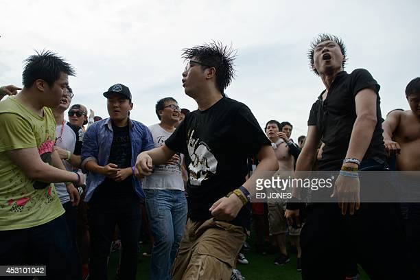 In a photo taken on August 2 rock fans listen to a performance by South Korean metal band Crash at the Pentaport Rock Festival in Incheon The annual...